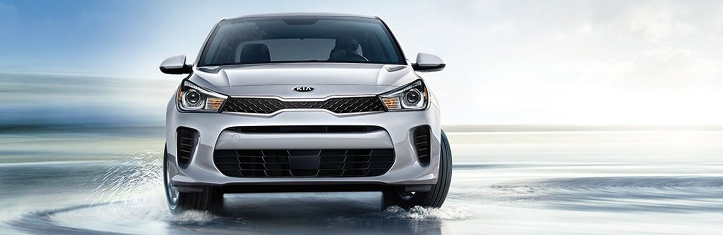 2019 Kia Rio exterior front shot of grille, headlights, and fascia with gray silver paint color as it turns and drives through shallow water on a beach