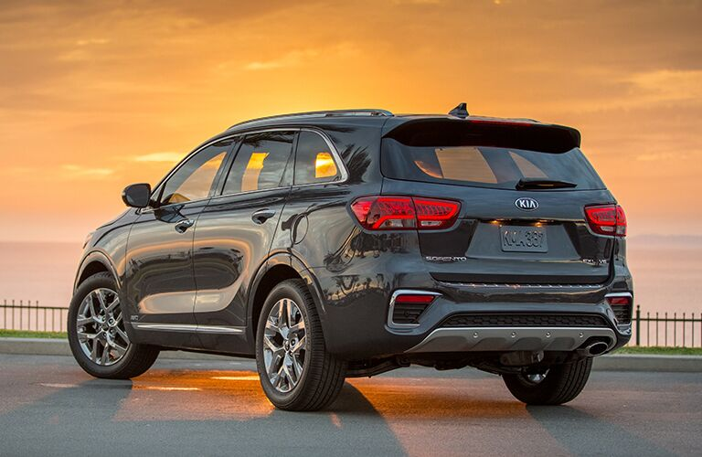 2019 Kia Sorento exterior shot rear of trunk, bumper, and lift gate parked by a fence as the sun sets in the sky