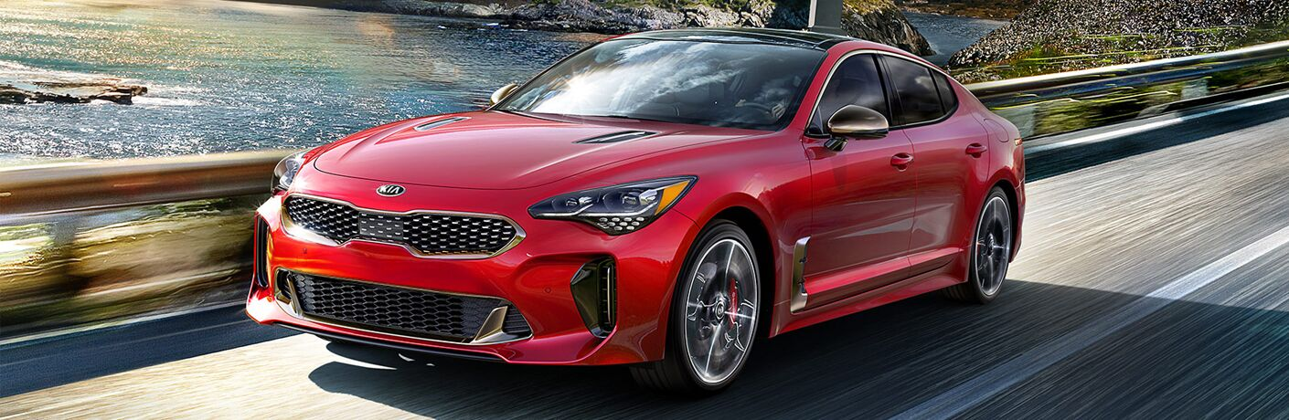 2019 Kia Stinger GT with HiChroma Red paint color exterior shot driving near a beautiful sea, sunshine, and arching bridge