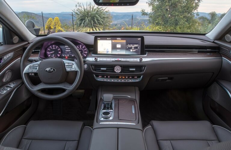 2019 Kia K900 interior shot of steering wheel, dashboard technology, and transmission knob
