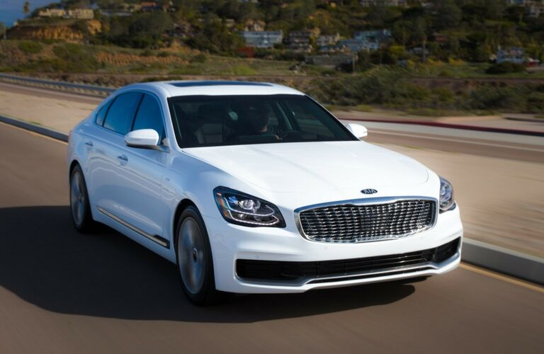2019 Kia K900 exterior shot with bright white paint color driving down a highway