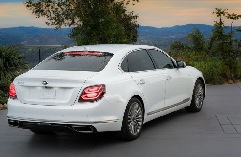 2019 Kia K900 exterior rear shot with bright white paint color parked near shrubbery at sunset