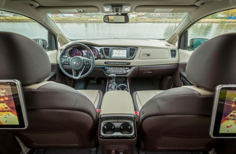2019 Kia Sedona interior shot front seating, rear entertainment system, dashboard, monitor, and outside view of a lake