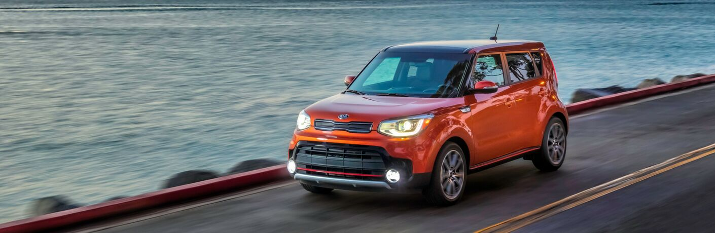 2019 Kia Soul exterior shot with orange paint color driving down a highway road next to the ocean or sea