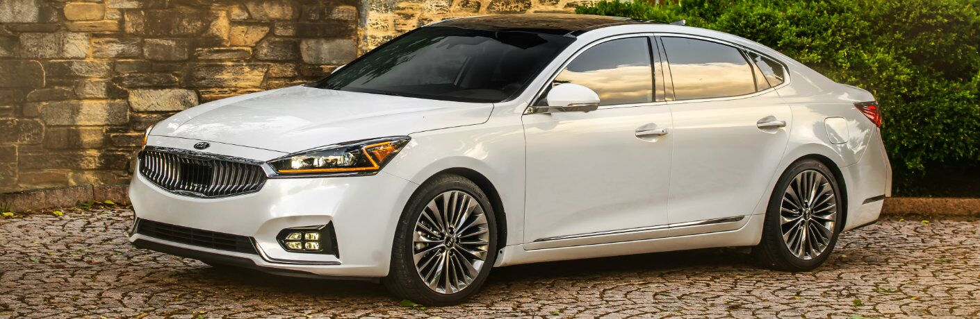 2019 Kia Cadenza exterior shot with white paint color parked on a tile driveway outside a stone country house