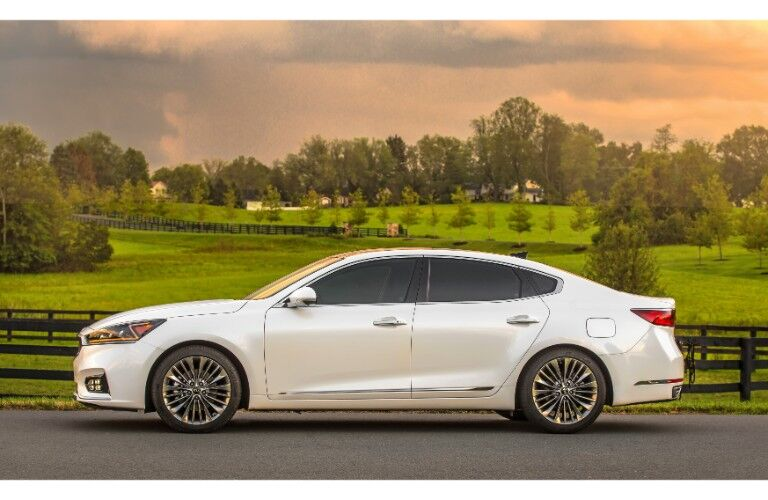 2019 Kia Cadenza exterior side shot with white paint color parked on an asphalt road near a wooden fence with farm land and forests behind it