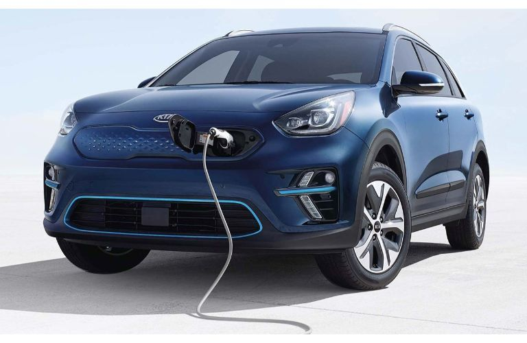 2019 Kia Niro EV exterior shot with blue paint color plugged in and charging