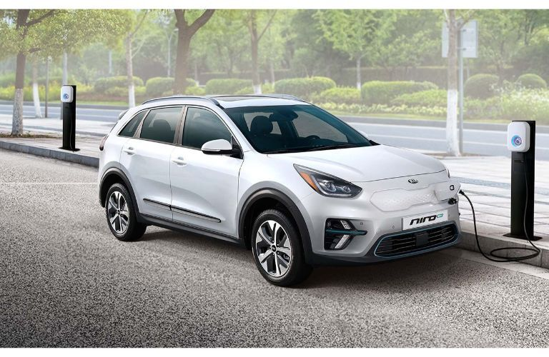 2019 Kia Niro EV exterior shot with white paint color plugged into a charging station in a park