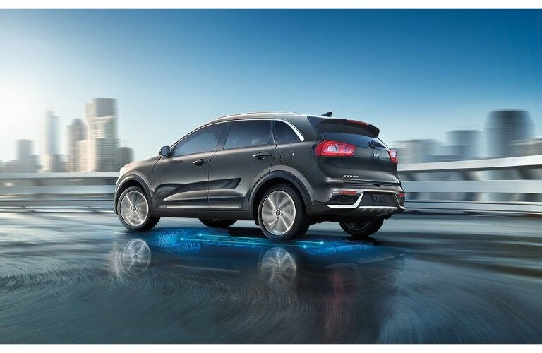 2019 Kia Niro exterior shot turning on wet ground with regenerative braking system lit up and a cityscape in the background