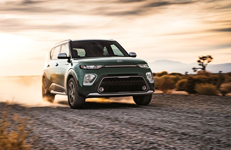 2020 Kia Soul exterior shot with forest green paint color driving on a gravel road as tires kick dust up