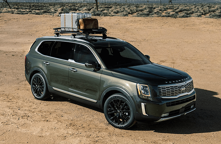 2020 Kia Telluride exterior overhead with forest green paint color parked in the desert with luggage strapped to its roof rails
