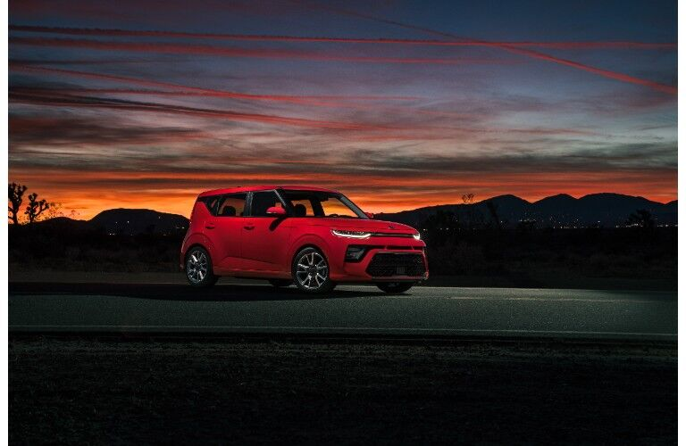 2020 Kia Soul GT-Line exterior side shot with red paint color parked outside under a colorful sunset sky