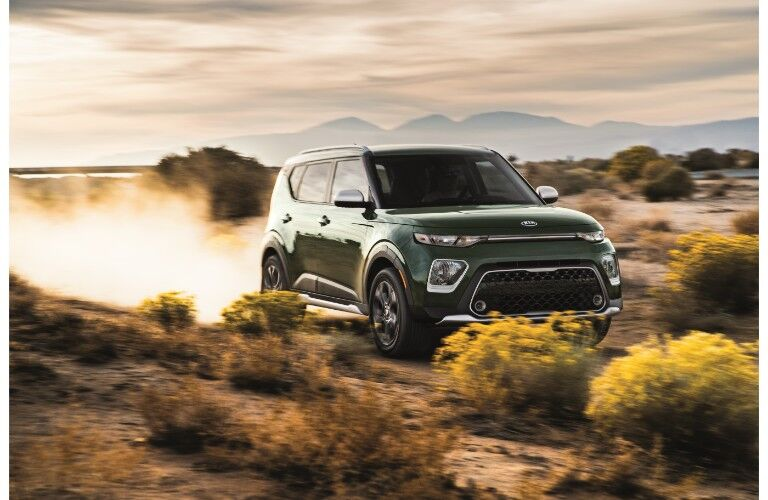 2020 Kia Soul X-Line exterior shot with green paint color driving through the desert as dust kicks up behind its wheels