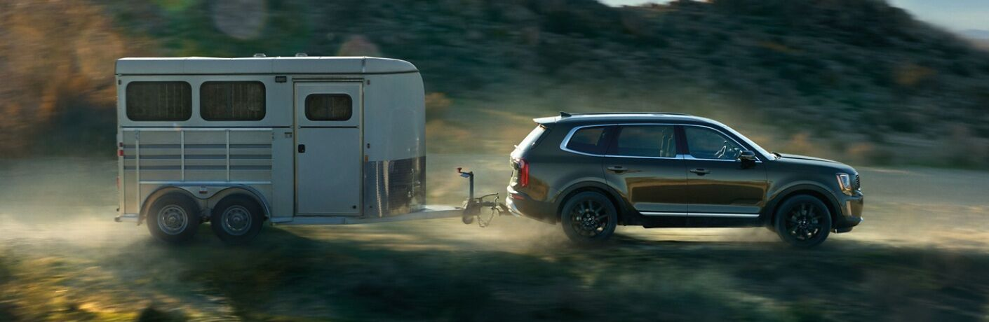 2020 Kia Telluride with a trailer hitch towing a trailer green side view