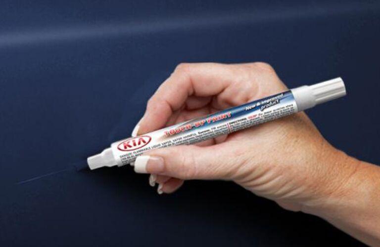 Kia paint pen on a blue vehicle surface