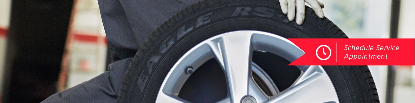 Tech rolling a wheel and tire schedule service appointment