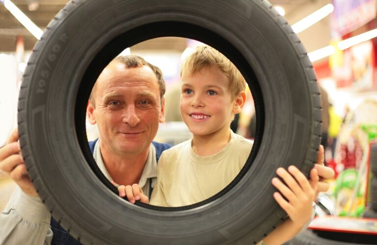 man and boy looking through a tire