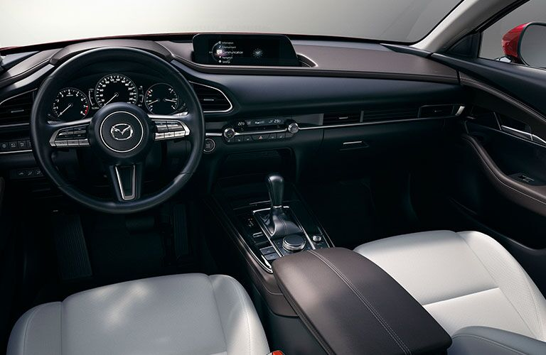 The front interior view of the steering wheel and center console of a 2020 Mazda CX-30.