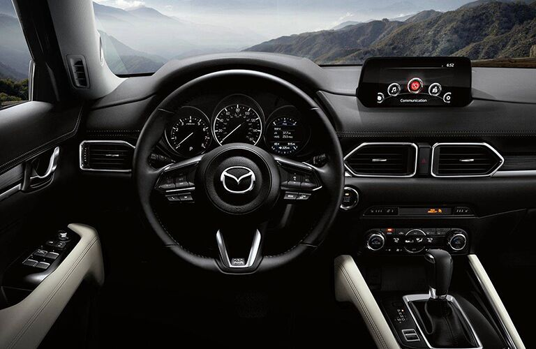 2018 Mazda CX-5 interior front seating view of steering wheel, infotainment system, dashboard, and transmission