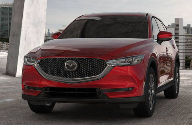 2018 Mazda CX-5 exterior soul red parked in an upper parking garage with a cityscape background