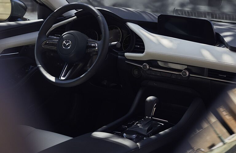 2019 Mazda3 interior shot of dashboard layout, steering wheel, and transmission with accent trimming