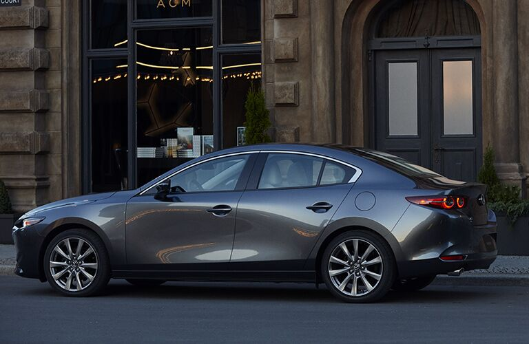 2019 Mazda3 sedan exterior side shot with gray metallic paint color parked next to a brown stone building