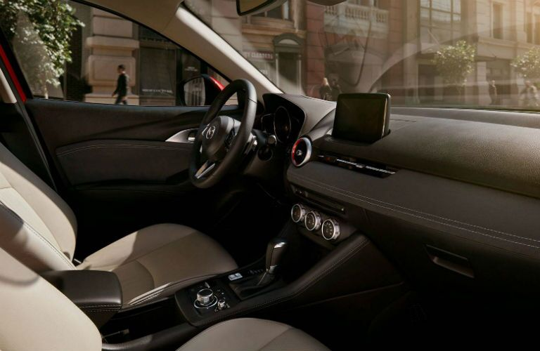 2019 Mazda CX-3 interior side shot of front driver's seat including steering wheel, transmission mission, and dashboard with mazda connect infotainment display screen