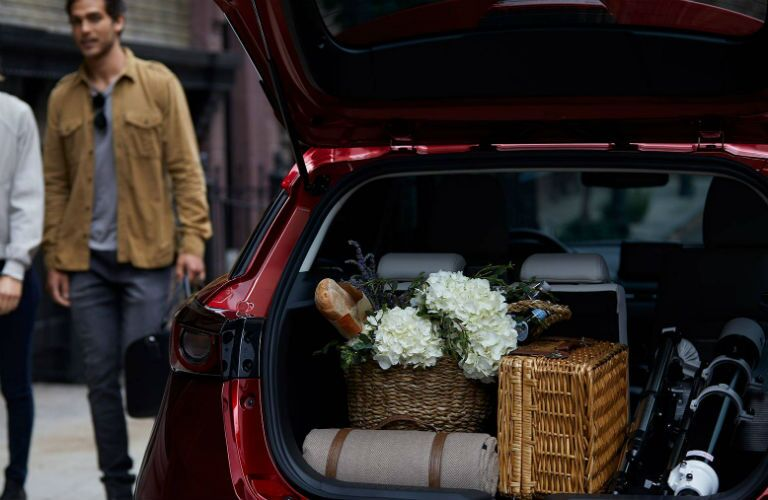 2019 Mazda CX-3 exterior shot of trunk opened up and loaded with luggage and knick knacks as 2 men approach