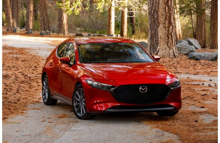 2019 Mazda3 hatchback exterior shot with red paint color parked in a forest as the sun shines in