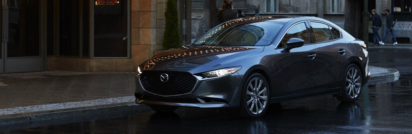 2019 Mazda3 sedan exterior shot with gray metallic paint color parked on a rainy street outside a lit up old world theater