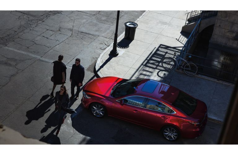 2019 Mazda6 sedan exterior overhead shot with soul red crystal paint color as a few pedestrians pass by on the sidewalk