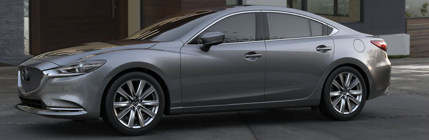 2019 Mazda6 sedan exterior side shot with gray metallic paint color parked outside a luxury villa built on a hill