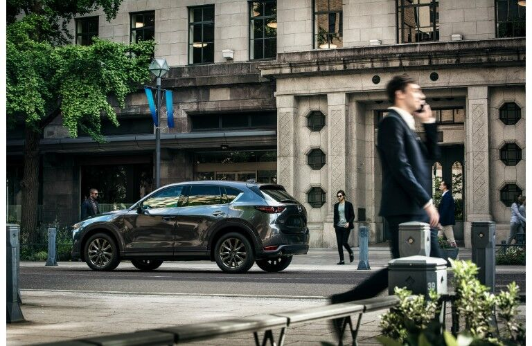 2019 Mazda CX-5 signature trim with gray metallic paint color exterior side shot parked near a intricate stone crafted building as city dwellers walk and commute by