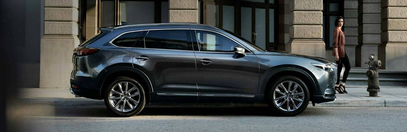 2019 Mazda CX-9 SUV exterior side shot with gray metallic paint job parked on a street near a fire hydrant as a woman walks by