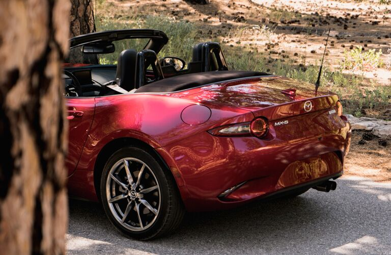 2019 Mazda MX-5 Miata exterior shot red paint job close up of back bumper, trunk, and soft top hood down