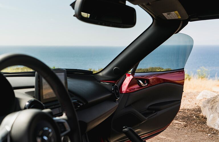 2019 Mazda MX-5 Miata interior shot of front dashboard and steering wheel with passenger side door open