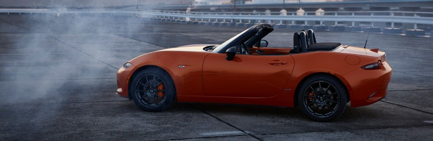 2019 Mazda MX-5 Miata 30th Anniversary exterior side shot with racing orange paint color parked on a race track as smoke from burnt rubber billows in the air