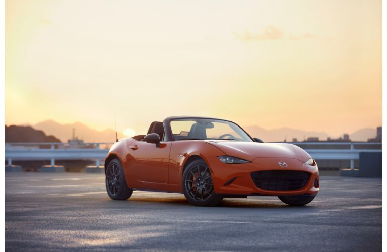 2019 Mazda MX-5 Miata 30th Anniversary special edition exterior shot with racing orange paint color parked on the top of a parking garage as a bright sun begins to set