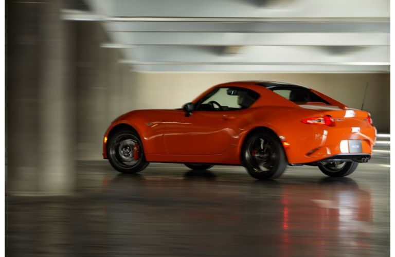 2019 Mazda MX-5 Miata 30th Anniversary special edition exterior side rear shot with racing orange paint color driving on a marble floor as the background blurs by
