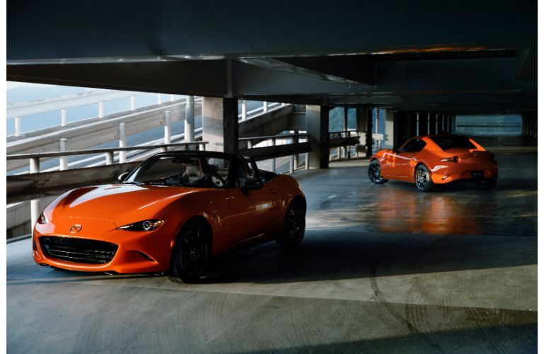 2019 Mazda MX-5 Miata 30th Anniversary special edition models parked in a dark parking garage with racing orange paint color