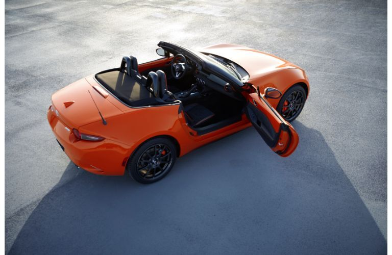 2019 Mazda MX-5 Miata 30th Anniversary special edition soft top exterior overhead shot with racing orange paint color as the sun draws its shadow across the blacktop of concrete