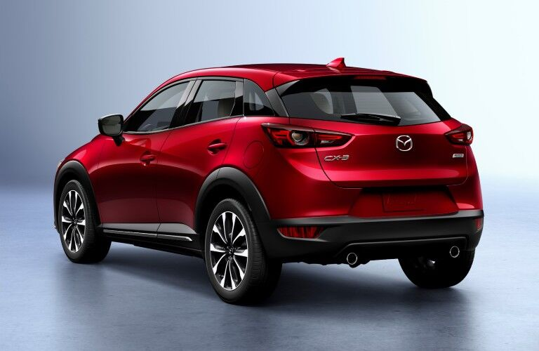 The rear and side view of a red 2020 Mazda CX-3.