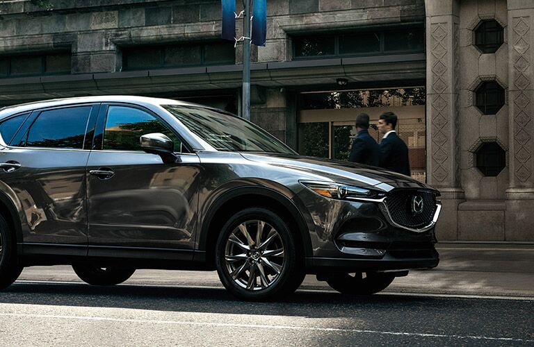 A front nd side view of a gray 2020 Mazda CX-5 parked on a city street.