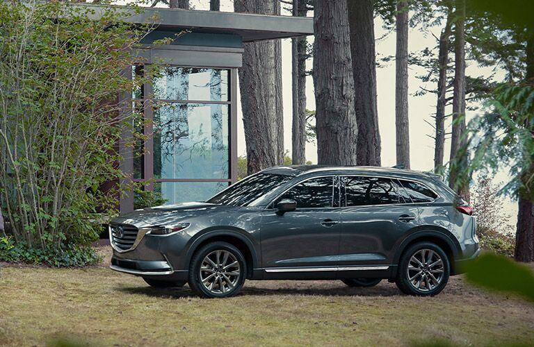 The front and side view of a grey 2020 Mazda CX-9 parked in a forest