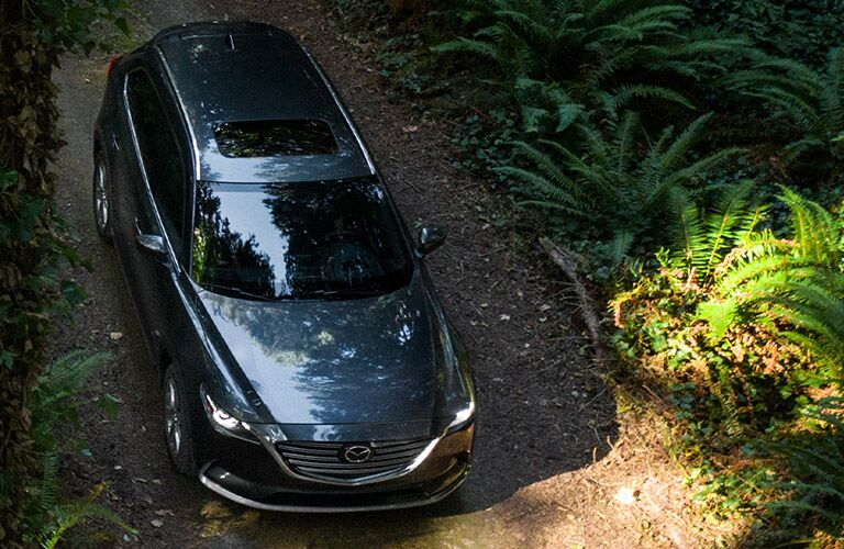 A front and top view of a gray 2020 Mazda CX-9 driving in a wooded area.