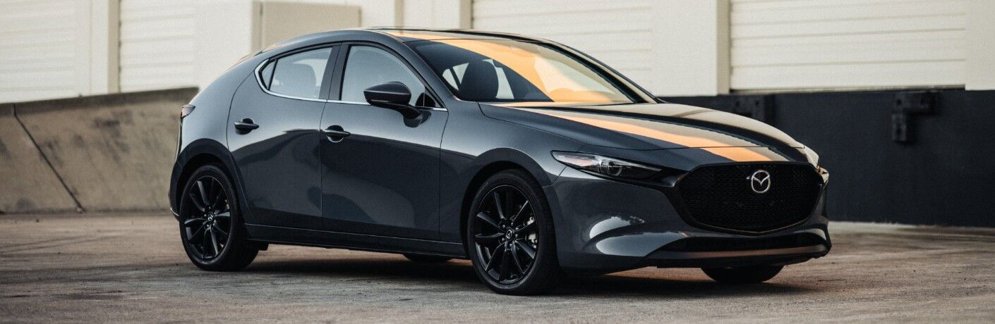 2020 Mazda3 hatchback exterior side shot with gray metallic paint color parked outside a white wood panel building