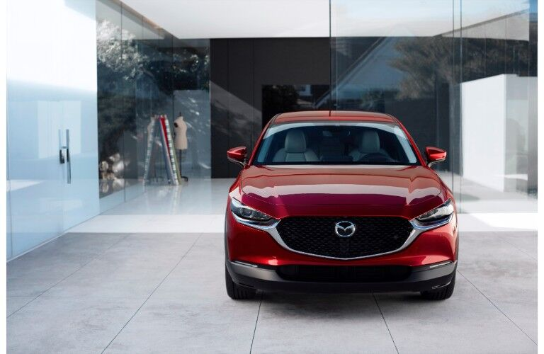 2020 Mazda CX-30 exterior front shot with red paint color parked inside a fancy home of white panels and glass