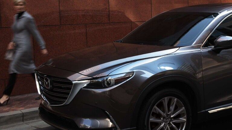 2020 Mazda CX-9 exterior side shot of headlight and grille design with gray metallic paint color parked on the side of a street as a pedestrian walks by