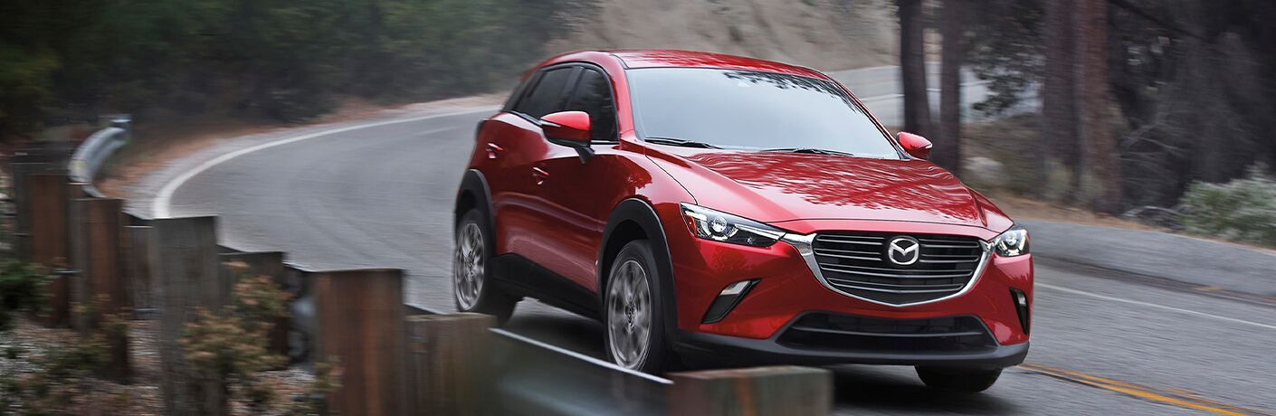 The front side of a red 2021 Mazda CX-3 driving quickly down an empty road.