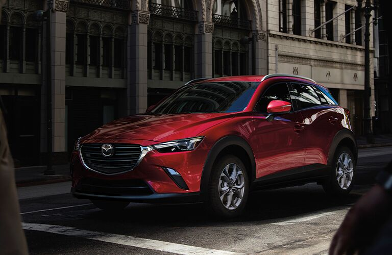The front view of a red 2021 Mazda CX-3 parked at an intersection.
